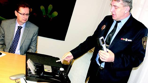 Milan Boháček z United Energy a velitel litvínovských strážníků Zdeněk Urban při včerejším představení nového alkohol testeru, který strážníci pořídili díky daru od teplárny.