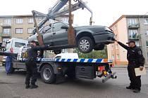 Městská policie Most nakládá vůz překážející při čištění v ulici Mladé gardy v Mostě.