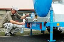 Odběr vody z cisterny na ulici.
