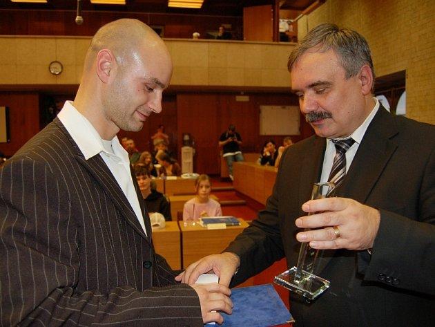Primátor Vlastimil Vozka předává cenu kickboxerovi Josefu Vitáskovi.