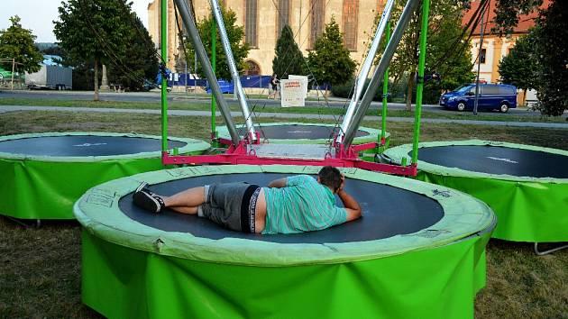 Muž unavený přípravou na Mosteckou slavnost u kostela odpočívá na trampolíně při západu slunce.