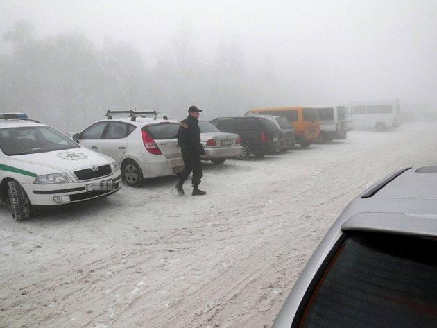 Policista prochází parkoviště na Klínech.