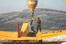 Ondřej Brzák pomáhá plnit letadlo vápencem na provizorním letišti. Letadlo vzlétá každých 10 minut.