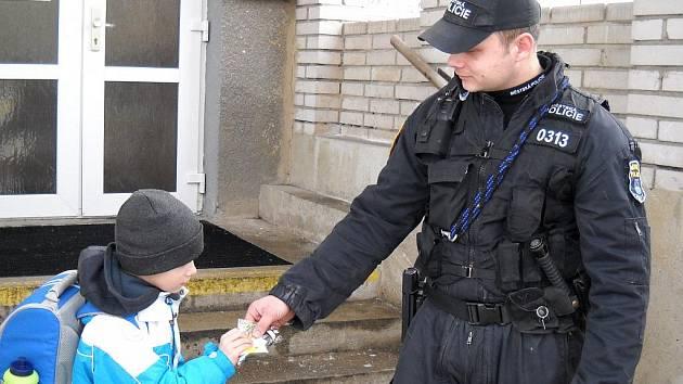 Mostecký strážník dává školákovi reflexní prvky.