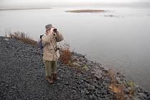 Ornitolog Jaroslav Bažant pozoruje ptáky u jezera Most.