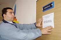 Na dveře sborovny ZŠ Janov vylepuje Marian Dancso plakátky s informacemi.