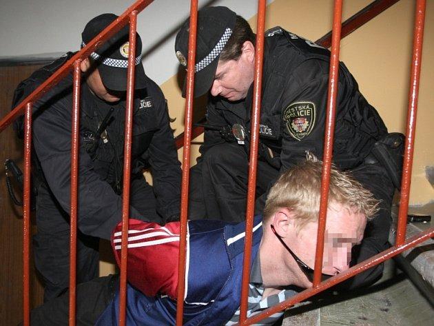 Strážníci krotí výtržníka, který na ně zaútočil šroubovákem na chodbě panelového domu v Janově.