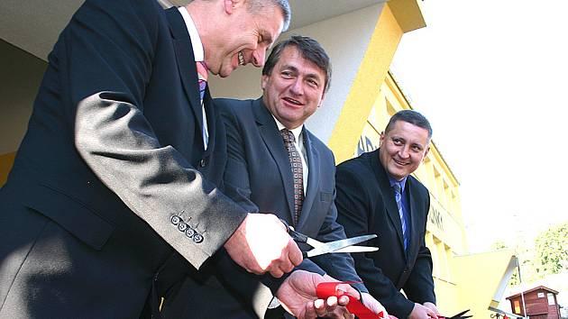 Starosta Litvínova Milan Šťovíček, hejtman Jiří Šulc a místostarosta Litvínova Martin Klika přestřihávají pásku před modernizovanou částí hokejového stadionu.