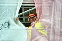 Dělník se usmívá při práci na nové fasádě Okresního soudu v Mostě.