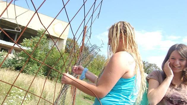 Markéta Vozková ukazuje, jak snadné je dostat se přes plot do ruiny objektu Zahražany.