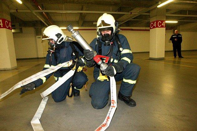 Hasiči nacvičují zásah v garážích mosteckého Centralu. Kvůli nebezpečí úniku plynu a následnému požáru do podzemí nesmí auta na plyn.