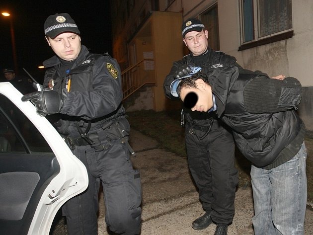Litvínovští strážníci odvádějí jednoho z dvojice pachatelů z místa činu.