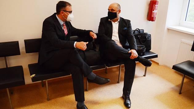 Josef Tancoš (vpravo) čeká na zahájení soudního líčení ve čtvrtek 21. května. Vlevo sedí jeho advokát.