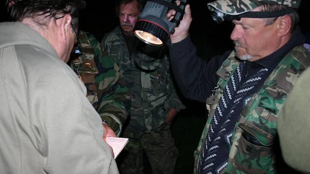Členové rybářské stráže vypisují protokol s rybářem (vlevo), kterého u Mariánských Radčic přistihli při lovu v nepovolenou noční dobu.