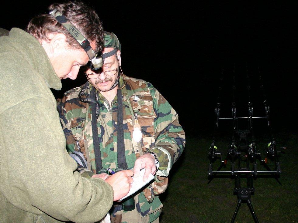 Šéf rybářské stráže Petr Bucha (vpravo) vypisuje protokol s rybářem, kterého u Mariánských Radčic rybářská stráž přistihla při lovu v nepovolenou dobu.