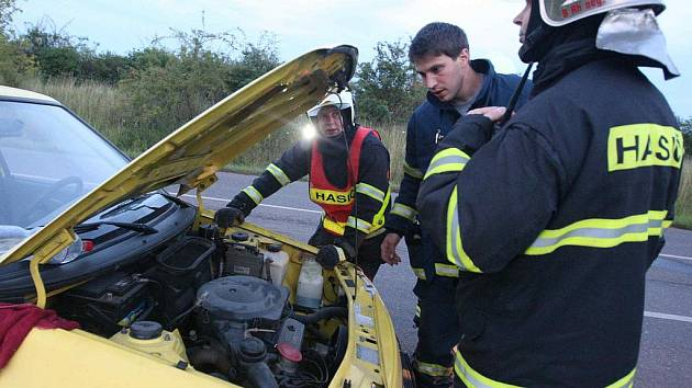 Hasiči kontrolují motorovou část vozidla po uhašení plamenů