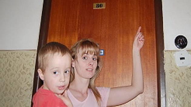 Julie Kuklová ukazuje na mezeru mezi dveřmi a rámem. Do bytu se může lehce dostat zloděj.