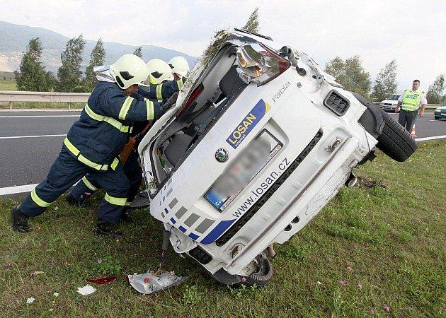 Hasiči převracejí nabouraný automobil na kola.