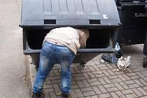 Muž si v Mostě naklonil popelnici, aby mohl sesbírat odpad na dně.
