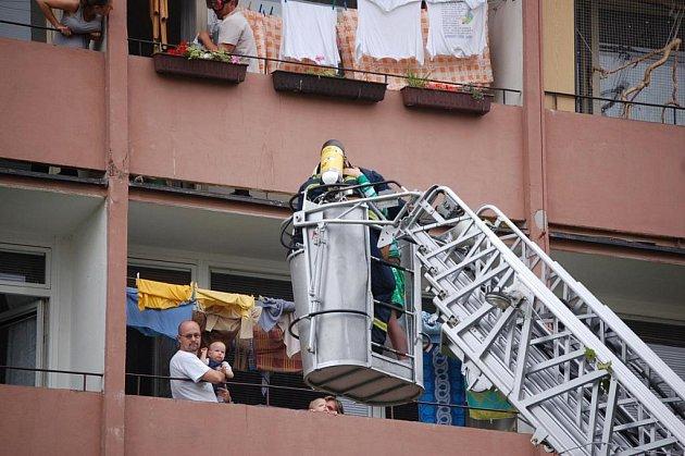 Hasiči zachraňují obyvatele panelového domu před nadýcháním kouřem.