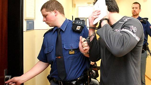 Justiční stráž vede obžalovaného Oldřicha Běhunka do soudní síně. Fotografem Deníku byl nepříjemně překvapen. Okamžitě si začal skrývat tvář.