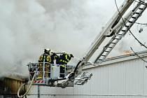 Hasiči bojují s plameny v továrně v Korozlukách.
