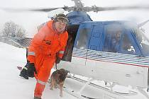 Záchranář se psem vystupuje z policejního vrtulníku.