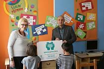 Ředitel firemní komunikace skupiny Unipetrol Jiří Hájek předává Marcele Stütz, ředitelce Dětského domova Most, výtěžek zaměstnanecké sbírky v hodnotě 130 590 korun