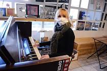 Klára Smrčková hraje na piano v opuštěné kulturní kavárně The Most café v centru Mostu.