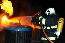 Hasič likviduje požár polopodzemního kontejneru.