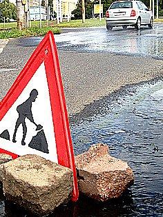 Značka upozorňuje řidiče na práce na silnici, kde teče z kanálu voda. Ještě se zde ale nepracuje.