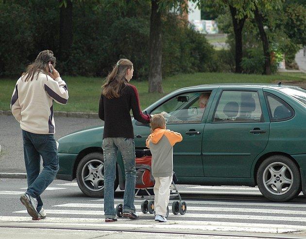 Ani mladá rodina s kočárkem se nedočká od řidiče přednosti. Vůz je přitom očividně ohrožuje a omezuje.