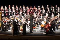 Plné pódium v Městském divadle v Mostě, kde byl poslední koncert 23. sezóny Mosteckých hudebních setkání. Vzadu vlevo ženský sbor Clavis Cordium z Mostu.