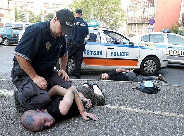Mostečtí strážníci zakročují proti výtržníkům.