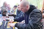 Zbyněk Sklenička podepisuje dres. V pozadí sedí Ondřej Jurčík.
