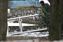 Muži v parku nad sportovní halou demolují hliníkové okno.