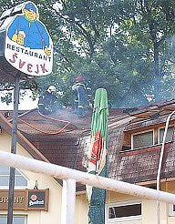 Hasiči likvidují požár v podkroví restaurace U Švejka.