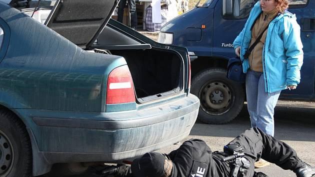 Strážník pomáhá ženě s porouchaným autem.