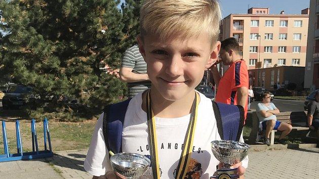 Osmiletý Tobias Student se usmívá s poháry před litvínovským plaveckým bazénem. Má důvod, vyhrál oba své závody.
