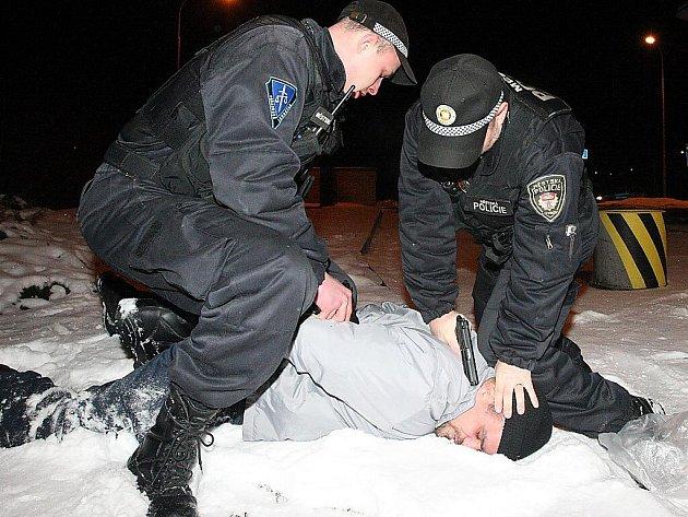 Strážníci nacvičují zadržení lupiče na litvínovské benzínce.