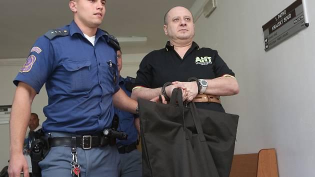 Eskorta odvádí obžalovaného Petra Mikoláše k zahájení procesu.