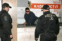 Strážníci kontrolují bezdomovce na nádraží.