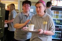 Zaměstnankyně kavárny míří za hosty. Sociální pracovnice jí ještě udílí pokyny. Ilustrační snímek