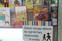 Děti si sami  knihu nekoupí. Vývěska na výloze v knihkupectví Dobrovský v  mosteckém Centralu jasně jejich vstup zakazuje.