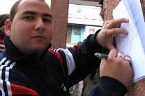 Jeden z nespokojených Litvínovanů podepisuje protestní arch. Nelíbí se mu, že místo peněžních sociálních dávek dostal kupony.
