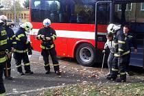 Hasič odvádí domů z evakuačního autobusu seniorku o berli.