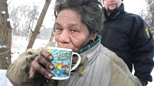 Bezdomovkyně pije horký čaj od strážníků.