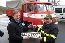Velitel hasičů města Olbernhau předává auto veliteli dobrovolných hasičů Brandova Jiřímu Hofmanovi.