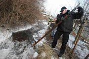 Dobrovolní hasiči a strážníci odstraňují ledové kry z potoka v Litvínově