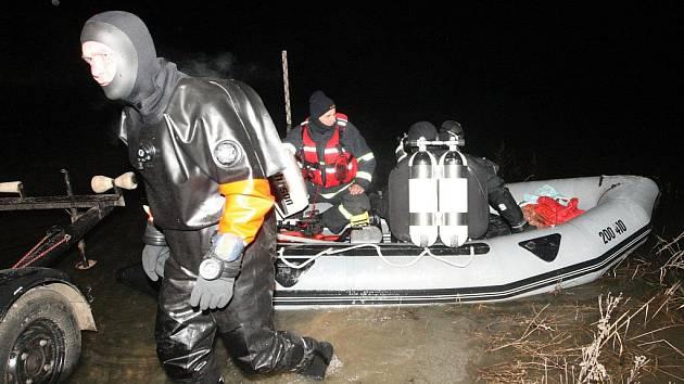 Potápěči prohledávají vodu napouštěného mosteckého jezera.